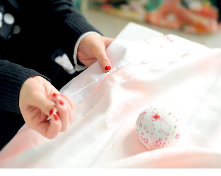 着物を縫う女性の手の写真